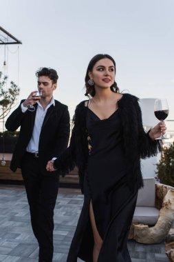 Mutlu kadın, terasta yürürken şarap içen adamla el ele tutuşuyor.