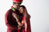 šťastný indický pár manžela a manželky v tradičním oblečení objímání izolované na šedé