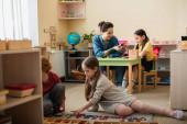 děti na podlaze hrát s dřevěnými písmeny v blízkosti učitel a dívka s pestrobarevnými kostkami na pozadí