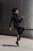 Side view of pretty african american sportswoman training on urban street