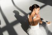 Hochwinkel-Ansicht der Ballerina sitzt auf grauem Hintergrund