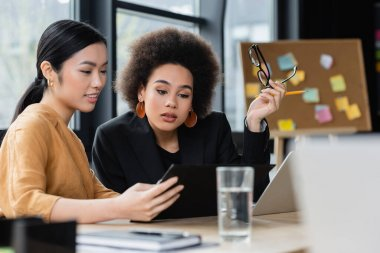 interracial businesswomen looking at clipboard while working in office