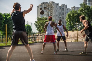 Interracial men playing basketball near friend with raised hands on blurred foreground