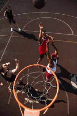 Overhead view of interracial men playing basketball near hoop