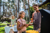 Smiling father holding grilled vegetables near grill and daughter outdoors