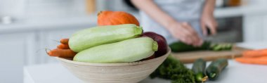 selective focus of bowl with fresh vegetables near blurred woman preparing breakfast, banner