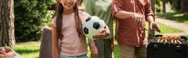 Cropped view of kid holding football ball near parents cooking on grill, banner