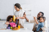 Afrikanerin hilft Tochter beim Einpacken des Rucksacks in Küche