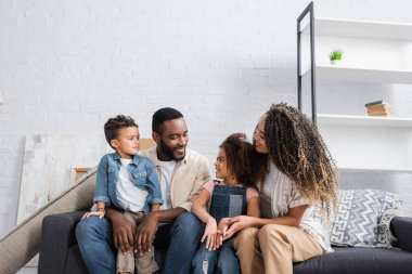happy african american family talking on couch in new apartment