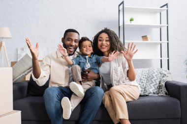 joyful african american family waving hands on couch in new apartment
