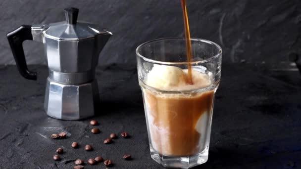 Nalil do sklenice s zmrzlina mražená káva se šlehačkou a čokoládovou polevou, podávaný s kávová zrna černém pozadí