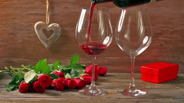 Valentines days arrangements with red roses and two wine glasses over gray background