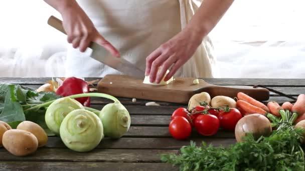 Nő szelet zöldség. Nő szelet hagymás fából készült asztal. Rusztikus stílusban.