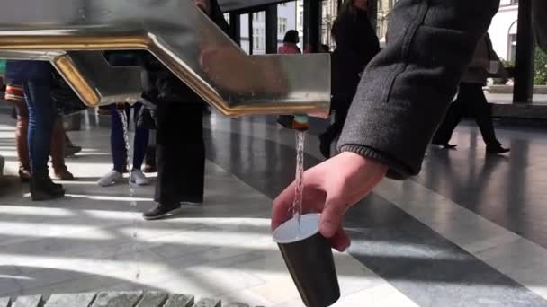 Prameny minerální vody tekoucí do skla od Karlovy Vary (Karlovy Vary) Česká republika, zpomalené