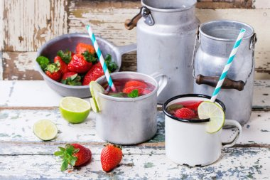 Vintage metal cups with retro cocktail tubes and water-cans of homemade strawberry lemonade, served with fresh strawberries, mint and lime over old white wooden table. See series stock vector