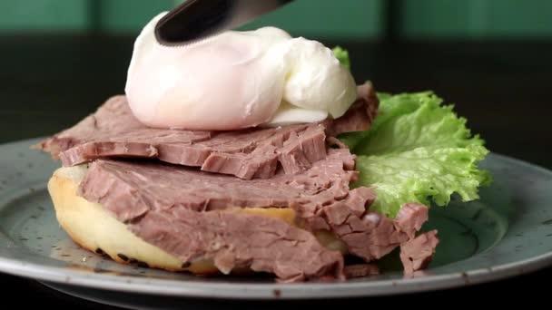 Piastra maculato con sandwich fatti in casa con carne cotta e liquido tuorlo duovo alla coque, insalata di spinaci