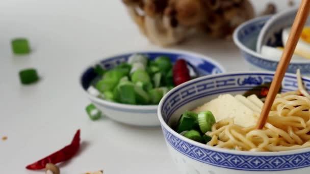 Vezmeme-bambusové hůlky nudle z asijských ramen polévku se sýrem feta, nudle, jarní cibulkou a houbami, podávané nakrájené vařené vejce bílý kuchyňský stůl