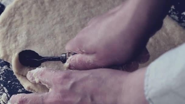 Ženské ruce krájení těsta na těstoviny od vintage převrátit černý stůl, hodlal mouky. Tmavý rustikální styl. V retro filtr efekt