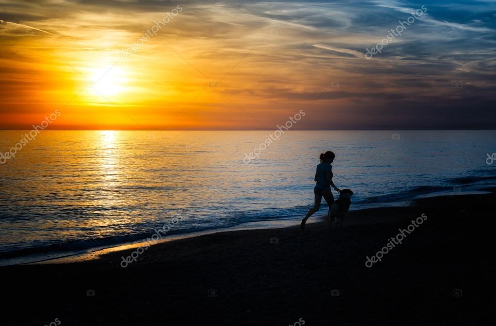 Girl runs with the dog on the beach