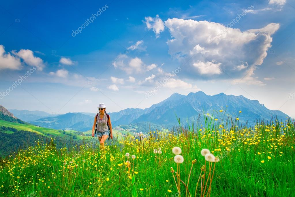 Alpine hiking lonely girl in a flowery meadow