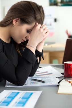 Tired female employee at workplace in office holding cup of tea