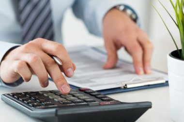 Close up of male accountant making calculations