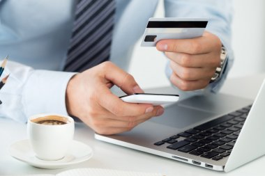 Close up view of businessman hands holding credit card and makin