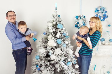 Happy family of four persons decorating christmas tree