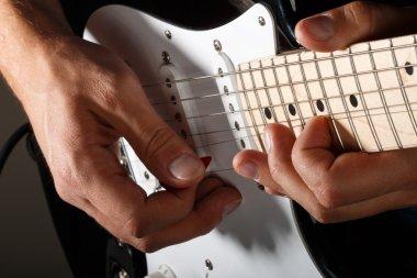 Hands of man playing electric guitar closeup