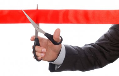 Hand of businessman in suit cutting red ribbon with pair of scis