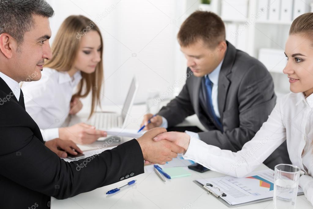 Businessman in suit shaking woman hand