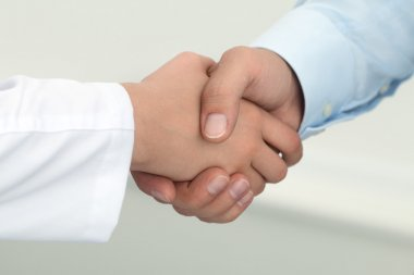 Female medicine doctor shaking hands with male patient.