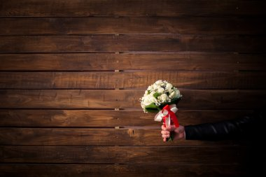wedding bouquet of white roses in groom's hand on wooden wall