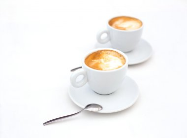 Two white cups of Cappuccino coffee with heart shaped milk foam