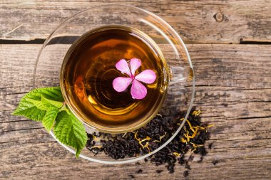 Glass Cup Tea with pink flower and Mint Leaf, on brown wooden pa