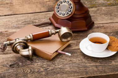 ivory tea cup with sweet cookie, old telephone and book on woode