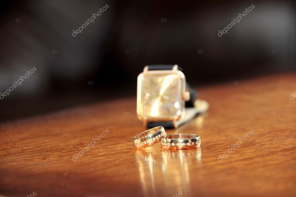Wedding ring and man watches on wooden the table