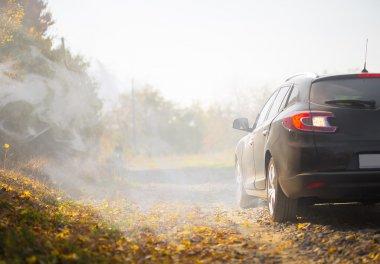 The car on old road near autumn park with fog