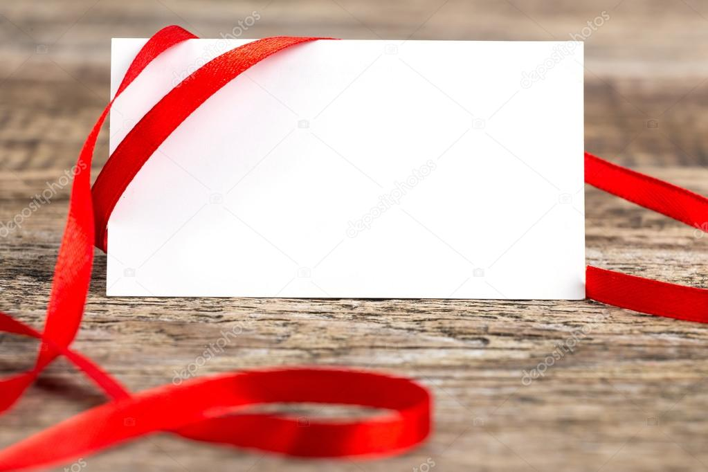 close up of card note with ribbon on wooden desk