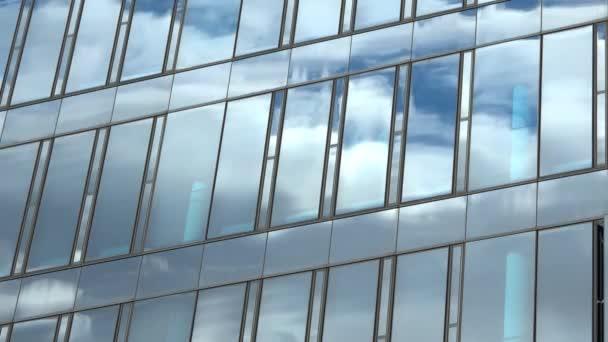 Časová prodleva a fasáda administrativní budovy odrážející letní oblohu
