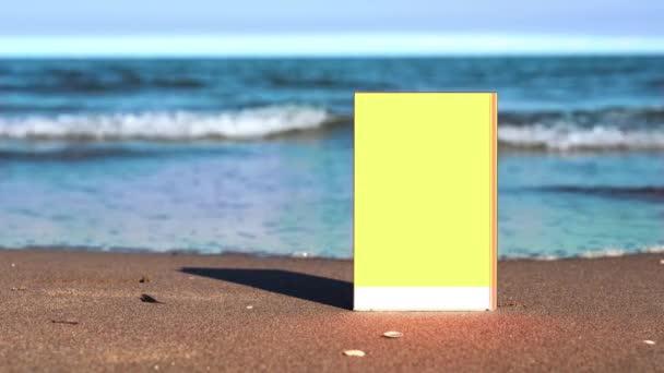 Sárga és fehér könyv áll a homokos tengerparton tenger ellen