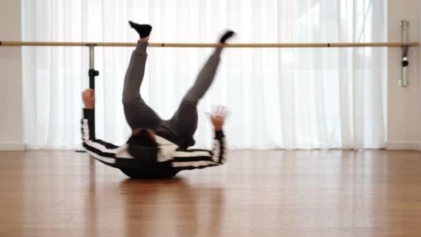 Professionelle Tänzerin übt auf dem Boden rotierende Bewegungen