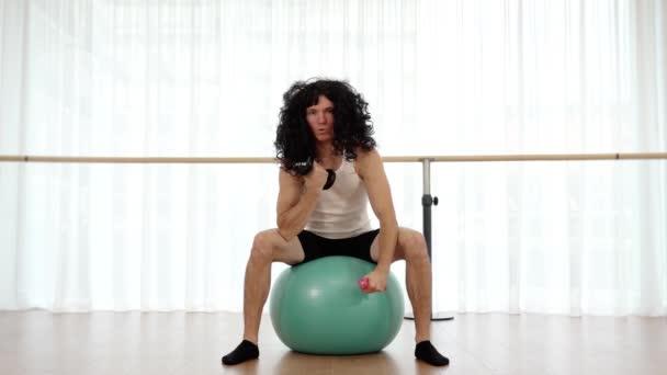 Sportlicher Athlet mit Langhaarperücke übt mit Hanteln