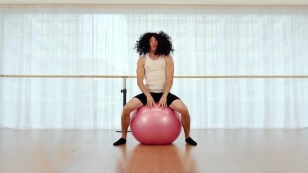 Lustiger Mann mit Perücke macht Sportübungen auf Fitball im Fitnessstudio
