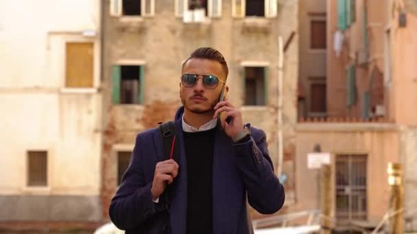 Vážný muž v slunečních brýlích s batohem rozhovory na telefonu