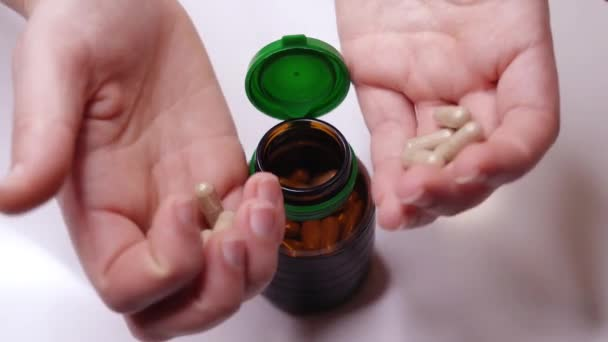Frau steckt verstreut rosa Vitamine in dunkle Glasflasche