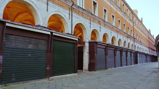 Malé obchody zavřené tmavými okenicemi ve starobylé budově