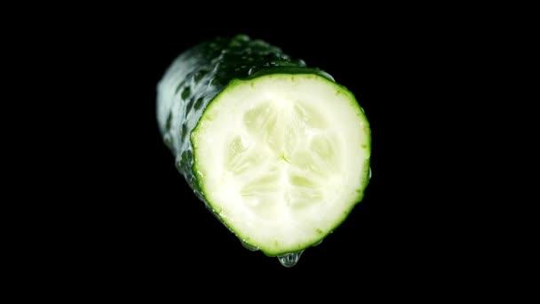 A fele ízletes törött uborka, vízcseppekkel a fekete
