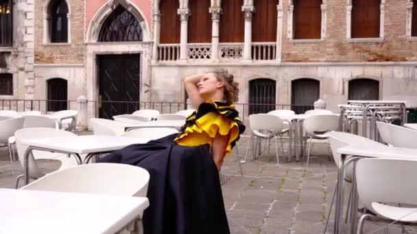 Dame in festlichem Kleid sitzt in leerem Café in Venedig