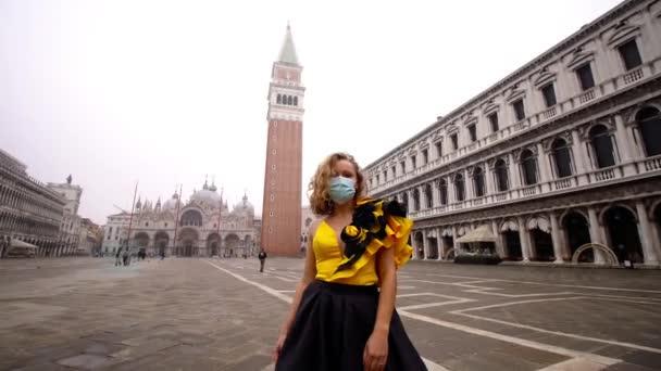 Model in Kleid und medizinischer Maske posiert auf leerem Platz in Venedig